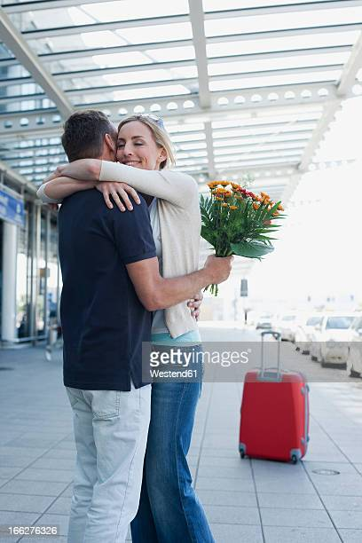 Germany, Leipzig-Halle Airport, Couple greeting in airport terminal