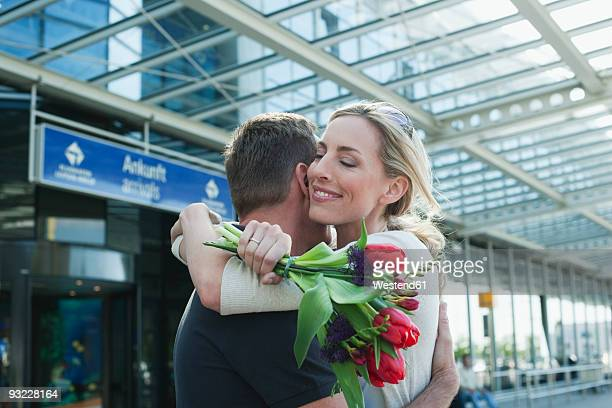 germany, leipzig-halle, airport, couple embracing, woman holding flowers - ankunft stock-fotos und bilder
