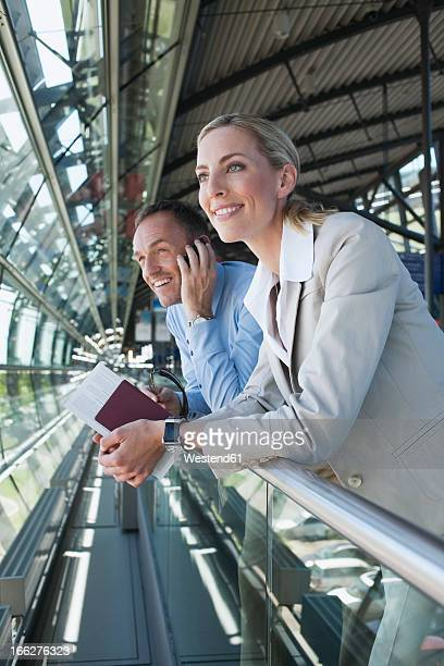 Germany, Leipzig-Halle Airport, Businessman and woman standing in airport terminal