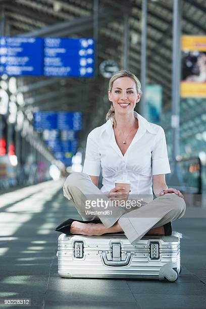 germany, leipzig-halle, young woman in airport departure lounge, sitting on suitcase - one mid adult woman only stock pictures, royalty-free photos & images