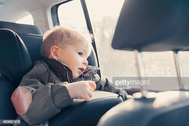 Germany, Little boy sitting in back-seat car seat