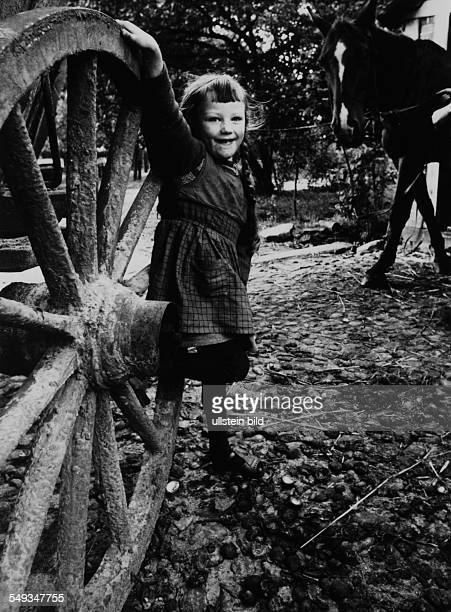 Germany little girl on the farm leaning at the wheel of a cart in the yard of the farmhouse in Lower Saxony