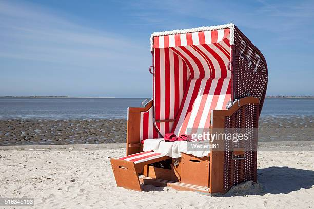 Germany, Lower Saxony, Dornum, Nessmersiel, red and white hooded beach chair
