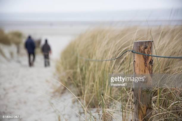 Germany, Lower Saxony, East Friesland, Langeoog, two people walking to the beach
