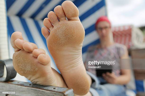 germany, lower saxony, east frisia, langeoog, woman reading e-book at the beach - female feet soles stock photos and pictures