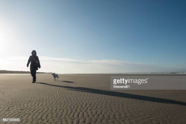 Germany, Lower Saxony, East Frisia, Langeoog, woman with dog on the beach