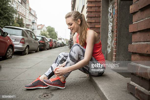 Germany, Lower Saxony, Hanover, young female jogger sitting on pavemant tying her shoe