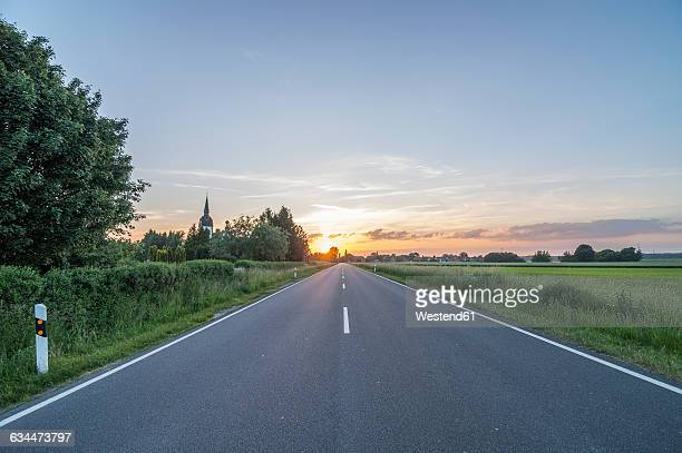 germany, lower saxony, peine, country road at sunset - country road stock pictures, royalty-free photos & images