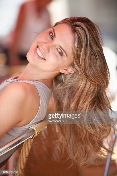 germany, lower-bavaria, landshut, close up of young woman sitting at street cafe, smiling, portrait - 頭をそらす ストックフォトと画像
