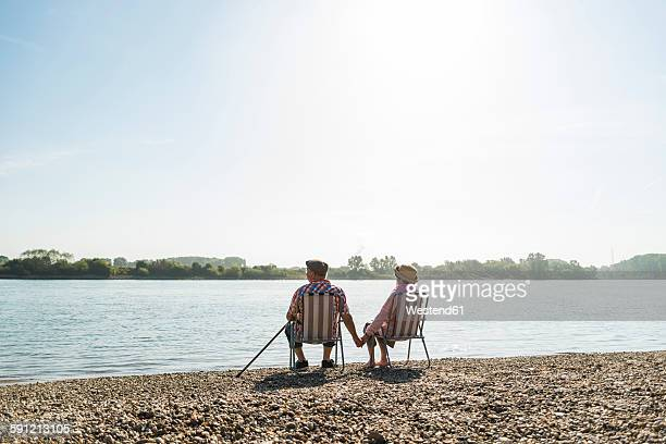 germany, ludwigshafen, back view of senior couple sitting hand in hand on folding chairs at riverside - cadeira dobrável - fotografias e filmes do acervo