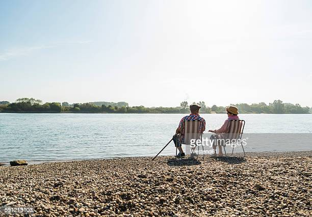 Germany, Ludwigshafen, back view of senior couple sitting side by side on folding chairs at riverside