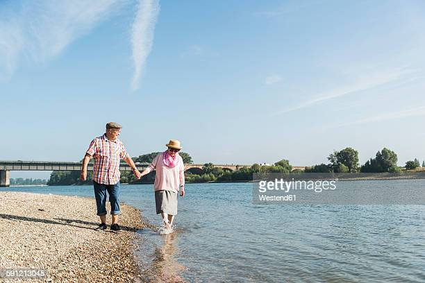 Germany, Ludwigshafen, happy senior couple walking hand in hand at riverside