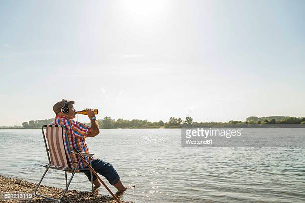 germany, ludwigshafen, senior man with headphones sitting on folding chair at riverside drinking beer - cadeira dobrável - fotografias e filmes do acervo