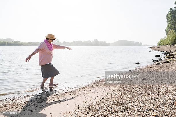 Germany, Ludwigshafen, senior woman walking out of Rhine River