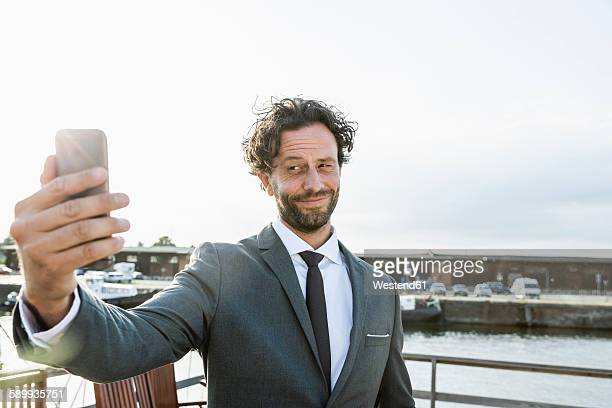 Germany, Luebeck, businessman at harbor taking a selfie