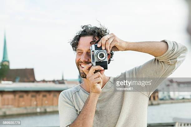 germany, luebeck, man taking picture at the waterside - fotograf stock-fotos und bilder