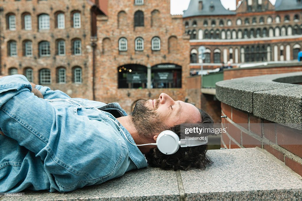 Germany, Luebeck, man with headphones relaxing in the city : Stock-Foto