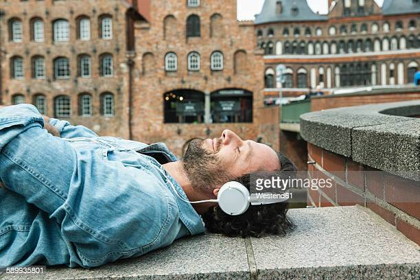 germany, luebeck, man with headphones relaxing in the city - city life stock-fotos und bilder