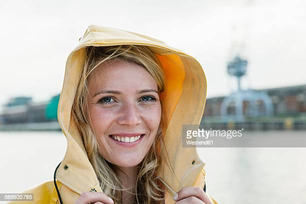 germany, luebeck, portrait of young woman wearing rain coat at the waterside - nordsee stock-fotos und bilder