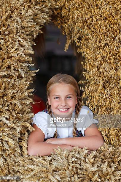 germany, luneburger heide, portrait of smiling blond girl in harvest crown - harvest festival stock pictures, royalty-free photos & images