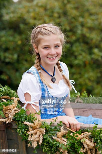 Germany, Luneburger Heide, portrait of smiling blond girl wearing dirndl sitting on harvest wagon