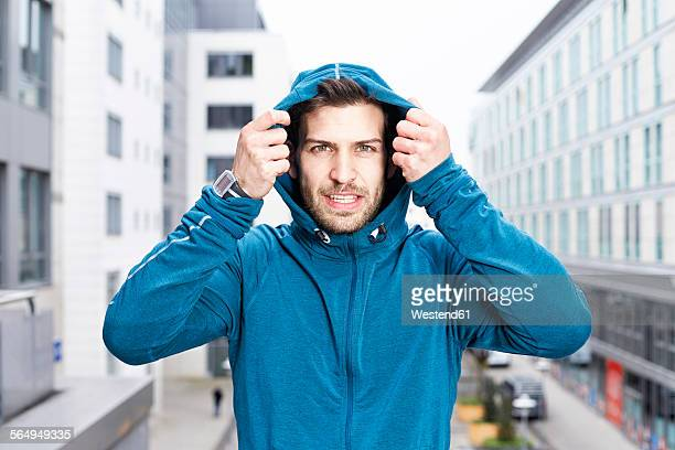 Germany, Magdeburg, portrait of young man wearing blue hooded jacket
