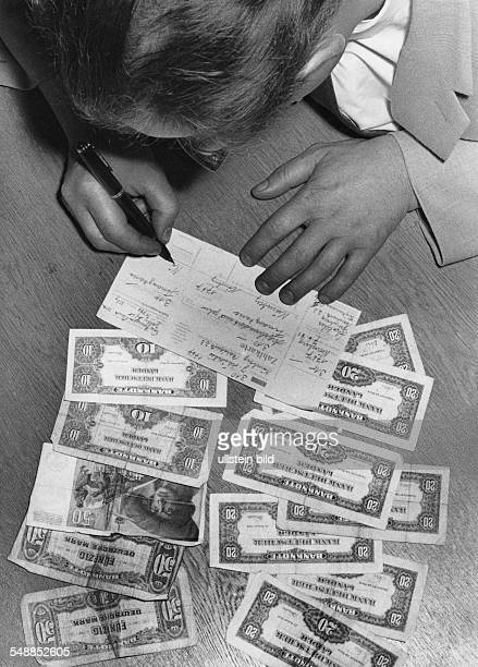 Germany man is filling in payingin slip 1950s