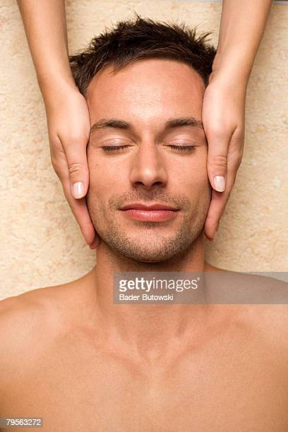 Germany, young man receiving facial massage, elevated view