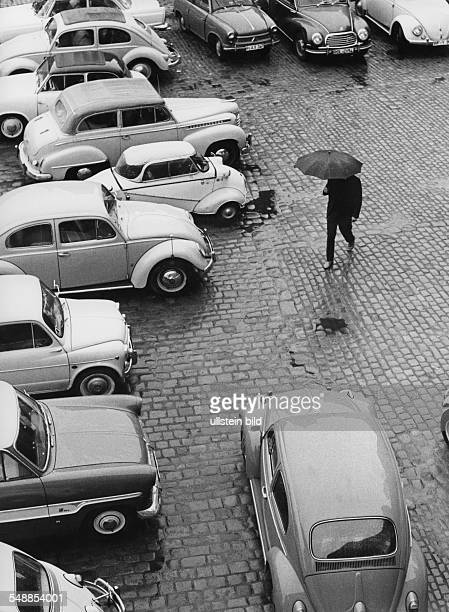 Germany man with umbrella is crossing a parking ground 1950s