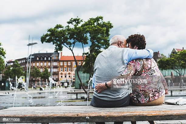 Germany, Mannheim, back view of kissing senior couple sitting on a bench hugging each other