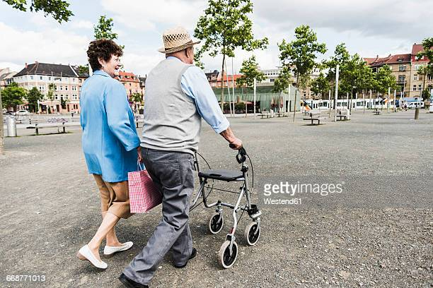Germany, Mannheim, back view of senior couple with wheeled walker