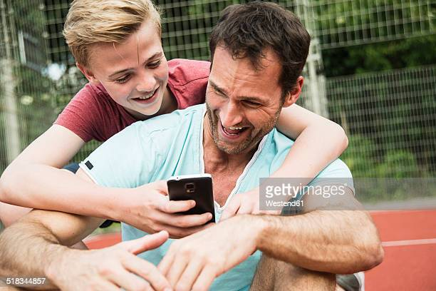 Germany, Mannheim, Father and son looking at smart phone