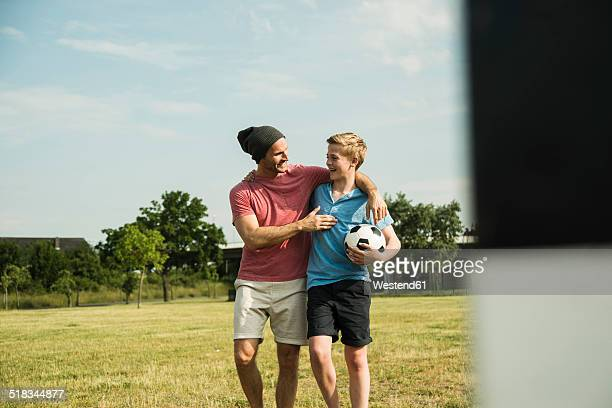 germany, mannheim, father and son playing soccer - dreiviertelansicht stock-fotos und bilder