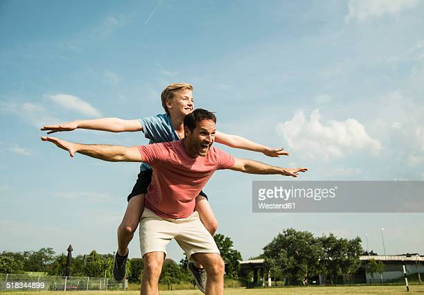 Germany, Mannheim, Father and son pretending to fly