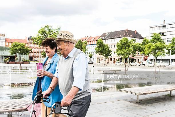 germany, mannheim, happy senior couple with wheeled walker - mannheim stock-fotos und bilder