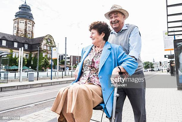 Germany, Mannheim, happy senior couple with wheeled walker waiting at station