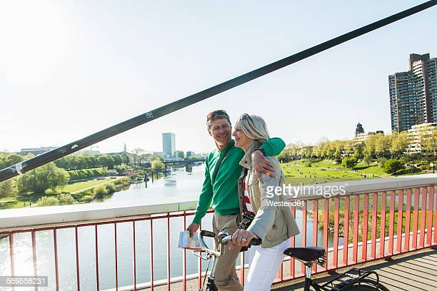 Germany, Mannheim, Mature couple crossing bridge, pushing bicycle