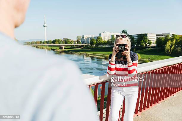 Germany, Mannheim, Mature couple taking city break, taking pictures