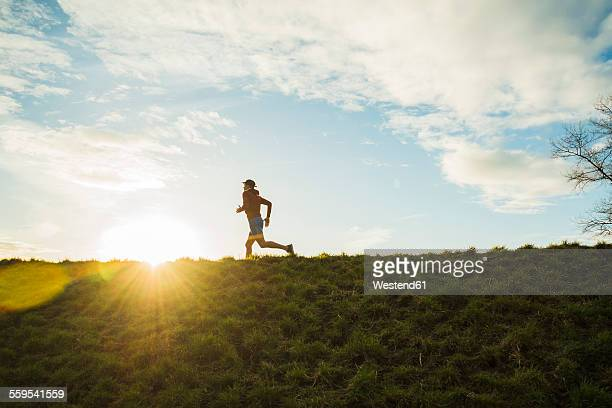 Germany, Mannheim, young man jogging at sunrise