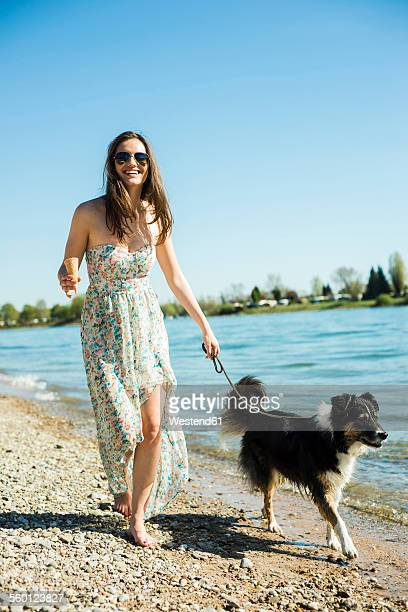 germany, mannheim, young woman walking with dog at river rhine - flussufer stock-fotos und bilder
