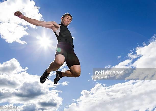 Germany, Mature man doing long jump