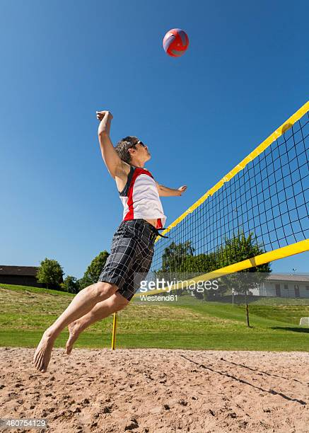 germany, mature man playing beach volleyball - strand volleyball der männer stock-fotos und bilder