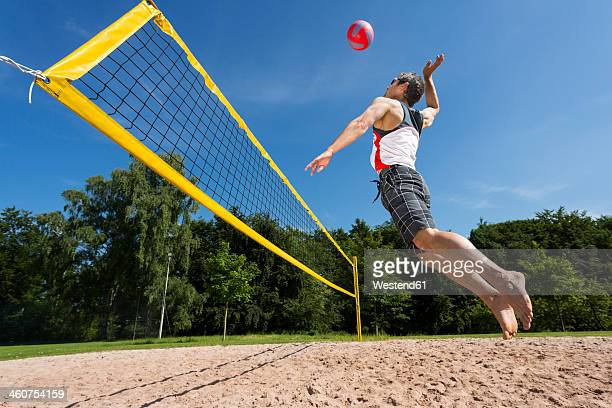 germany, mature man playing beach volleyball - strand volleyball der männer stock-fotos und bilder