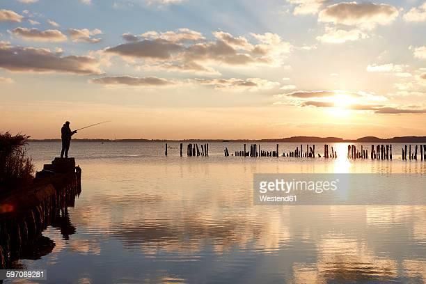 Germany, Mecklenburg-Western Pomerania, Ruegen Island, Glowe, Angler on Spyckerscher See at sunset