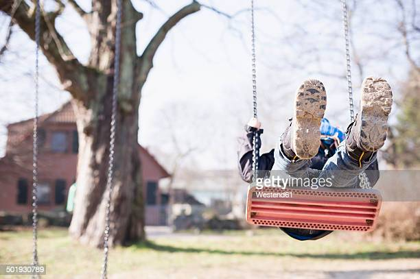Germany, Mecklenburg-Western Pomerania, Ruegen, little boy swinging at playground