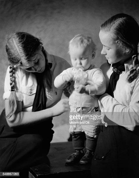 Germany Member of the Young Girls League caring for people with many children for the National Socialist People's Welfare Organization...