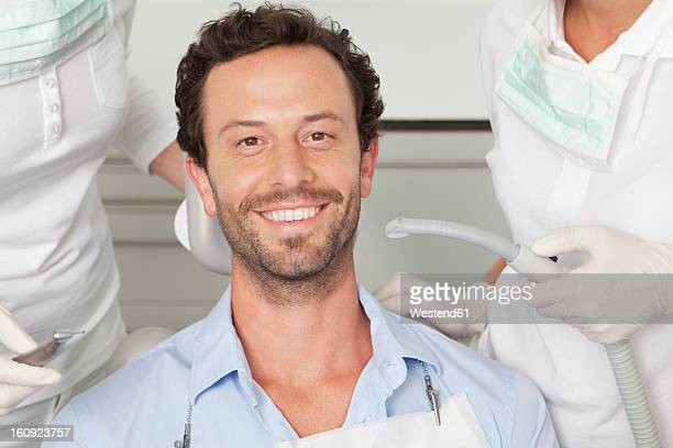 Germany, Mid adult man getting his teeth examined by dentist