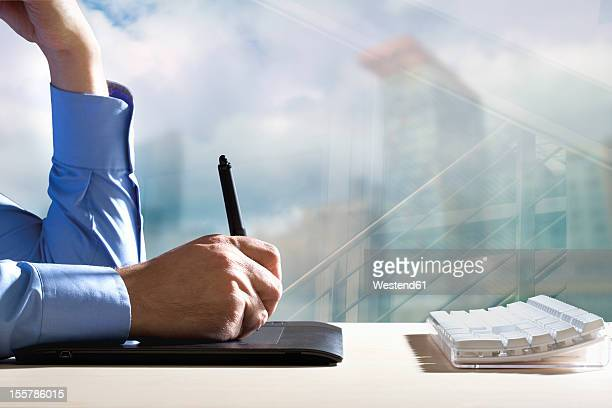 Germany, Mid adult man working with digital pad