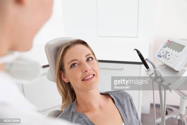 Germany, Mid adult woman in dentist chair, smiling