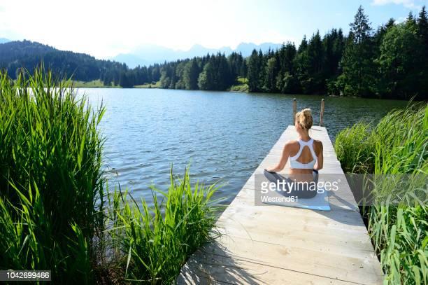 germany, mittenwald, back view of woman practising yoga on jetty at lake - bootssteg stock-fotos und bilder